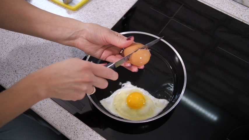 baharatlı alman sosisi : A woman breaks eggs in a hot pan. She is preparing breakfast. 4K Slow Mo Stok Video