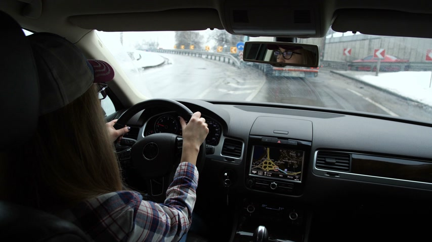 navigasyon : The girl goes on the highway. A lot of cars on the road. She follows the navigator and looks around. 4K Slow Mo