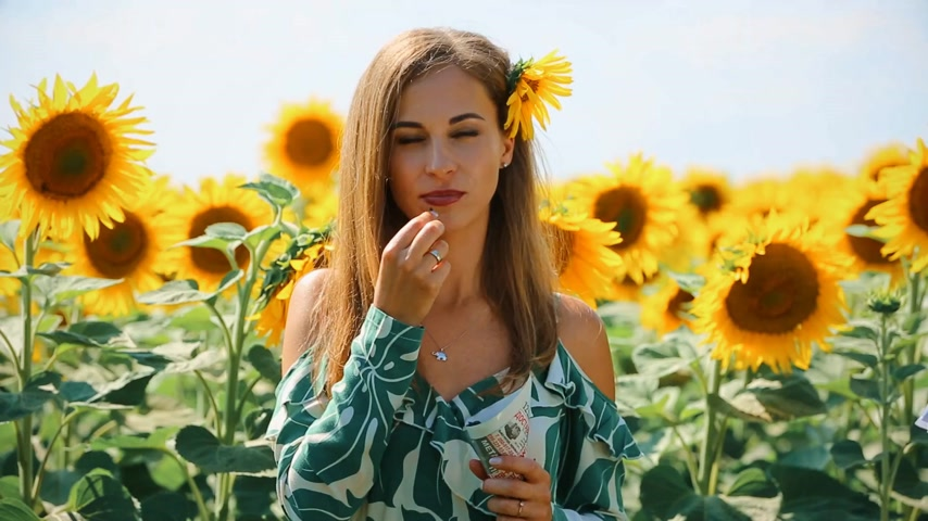 film şeridi : Storyboard with woman in sunflowers. Yellow field with sunflowers. In the foreground is a girl in a green dress and eating seeds. Stok Video