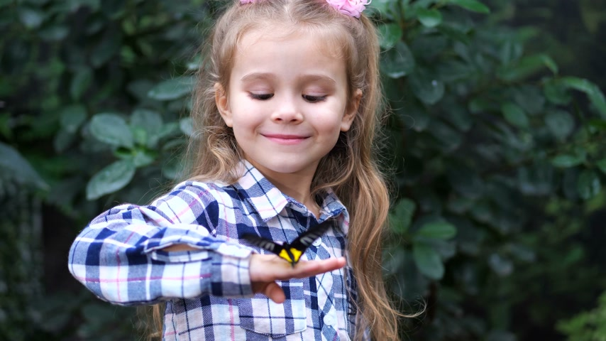 чешуекрылых : The little princess holds a butterfly on her hand, looks at the frame and smiles. 4K Slow Mo