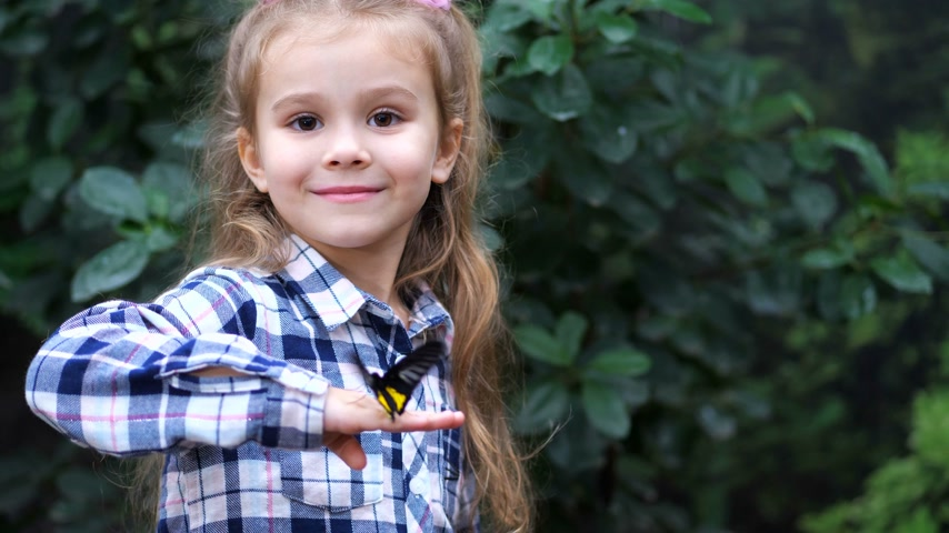чешуекрылых : A very cute girl holds a butterfly on her hand, turns to frame and smiles. 4K Slow Mo