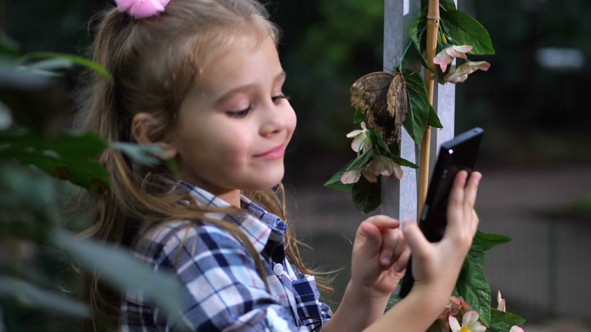 чешуекрылых : A girl takes a selfie with a butterfly. Baby posing in front of the screen. 4K Slow Mo