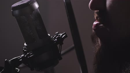 kondenzátor : Recording studio. Close-up. A man with a beard sings a song or reads the text into the microphone. 4K Slow Mo