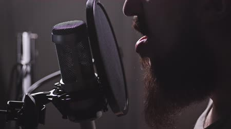 kondenzátor : A microphone in the studio, a man appears, starts reciting or humming. 4K Slow Mo Dostupné videozáznamy