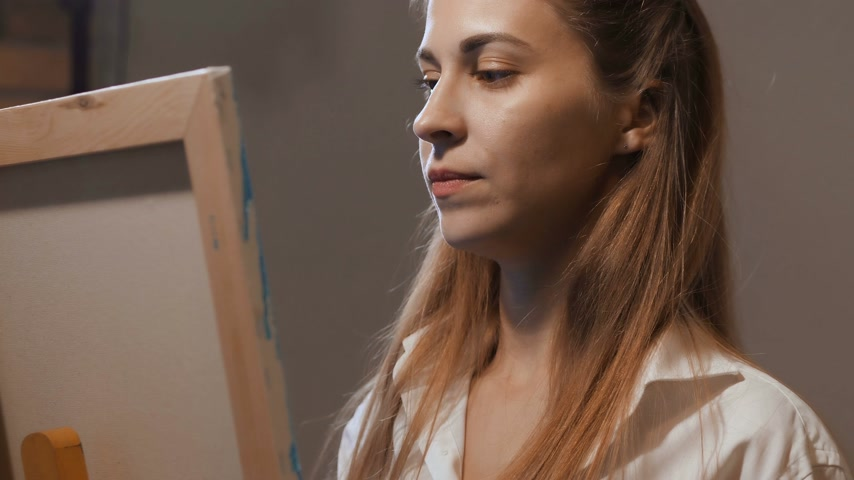 rascunho : Portrait of the artist. The girl stands at the easel, paints a picture, she is very interested. 4K Slow Mo Vídeos