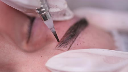 sterilità : Close-up. Applying paint on the eyebrow, permanent makeup. 4K Slow Mo Filmati Stock