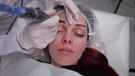 sterility : The face of a girl who does permanent eyebrow makeup. 4K Slow Mo Stock Footage