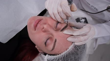 sterilità : Cosmetology salon, master special machine draws eyebrows. Permanent makeup. 4K Slow Mo Filmati Stock