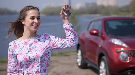 пожертвование : Happy girl shows the keys to a new car, in the background is a car. 4K Slow Mo