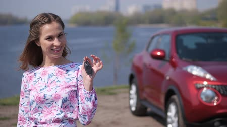 engedély : Beautiful girl shows car keys, looks into the frame and smiles. 4K Slow Mo Stock mozgókép