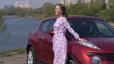 el arabası : The girl in a dancing mood is walking along the new car, spinning and leaning on the hood. 4K Slow Mo