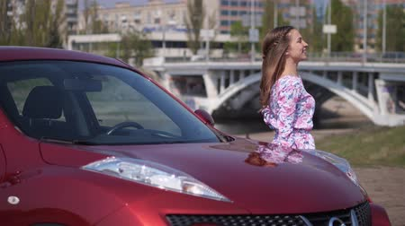 el arabası : A girl dances in front of a new car, lies on the windshield and hugs the car. 4K Slow Mo