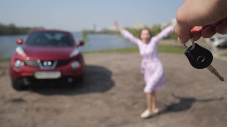 engedély : The girl saw a new car. The man is waving his keys, the girl picks them up and runs to hug the car. 4K Slow Mo Stock mozgókép