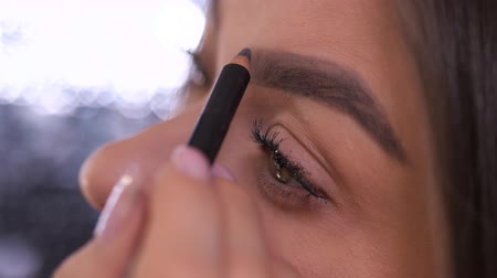 kaşları : Close up. Eyes, eyebrows. The girl paints an eyebrow shape with a pencil. 4K Slow Mo