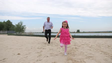 salie : Granddaughter and grandfather are running along the beach. They smile and have fun. 4K Slow Mo Stockvideo
