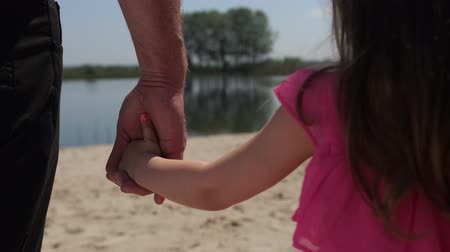 salvia : Close up. Granddaughter takes grandfathers hand. They go forward. Walking along the lake. 4K Slow Mo Filmati Stock