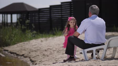büyükbaba : The girl runs to her grandfather, hugs his neck and smiles at the camera. 4K Slow Mo