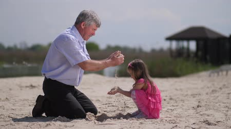 adaçayı : Girl with grandfather on the beach, they play sand. 4K Slow Mo