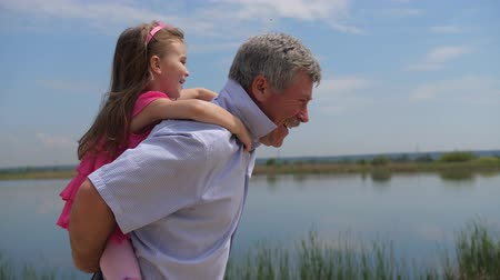 adaçayı : A little girl sits with her grandfather on her back, they run along the lake. 4K Slow Mo