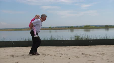 adaçayı : Little granddaughter sits on her grandfather. They run and have fun. 4K Slow Mo