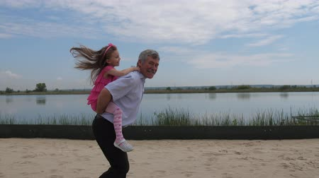 adaçayı : The camera is in motion. The girl runs along the beach with her granddaughter on her back. Little girl rejoices. 4K Slow Mo Stok Video