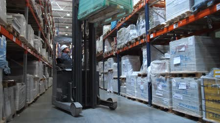 unload : Forklift lifts a large box on the top shelf. Behind the wheel of an employee. 4K Slow Mo Stock Footage