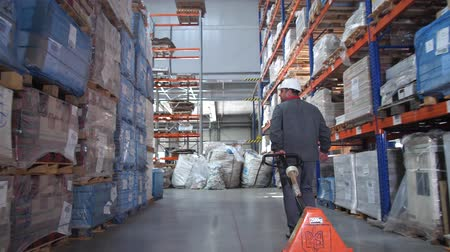przesyłka : A man carries a lift for pallets in a logistic warehouse. 4K Slow Mo