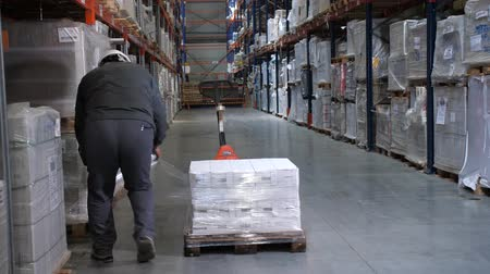 przesyłka : A man in a helmet and uniform packs a pallet. Logistics warehouse. 4K Slow Mo