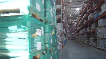 партия : Huge logistic warehouse. Panorama between the rows with shelves. The warehouse is filled with products in boxes. 4K Slow Mo