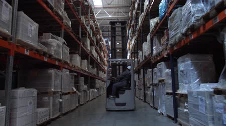 партия : Camera movement between the racks with the goods. Ahead is a man on a forklift. 4K Slow Mo