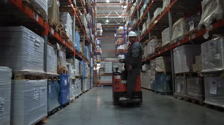 hard hat : The worker rides along the row along the high racks with the products. 4K Slow Mo Stock Footage