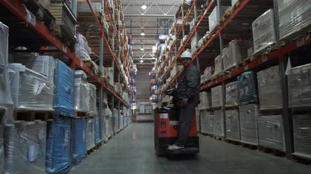 vorkheftruck : Incredibly large logistic warehouse. A man on a car passes by the camera. 4K Slow Mo