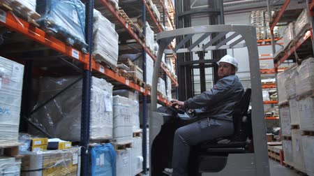 przesyłka : Warehouse worker riding a forklift along the pallet with the goods. 4K Slow Mo
