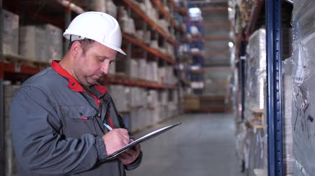 przesyłka : An employee at a logistics warehouse describes products. Close-up. 4K Slow Mo