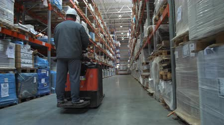 партия : A huge warehouse with goods. The worker in uniform and helmet moves on the square between the rows. 4K Slow Mo