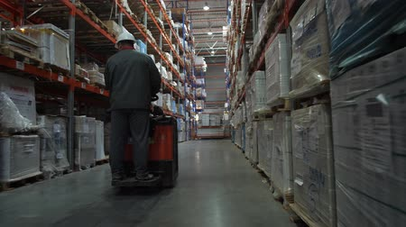 vorkheftruck : The worker rides on the square between the shelves filled with boxes of goods. 4K Slow Mo