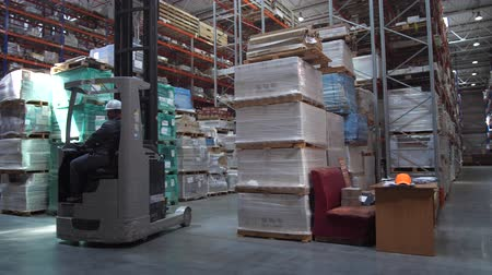 chariot elevateur : Travel worker on a forklift through the logistics warehouse. 4K Slow Mo Vidéos Libres De Droits