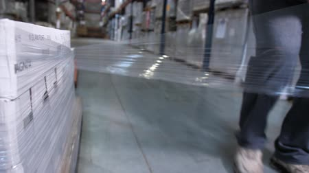 vorkheftruck : Close-up. A man is packing a pallet with boxes with plastic wrap. 4K Slow Mo
