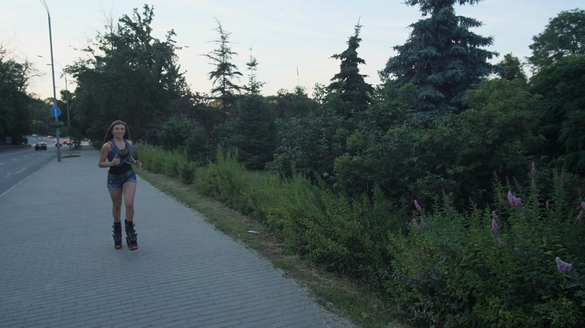 A girl in a special shoe, Kangoo Jump, runs along the path in the park. 4K Slow Mo