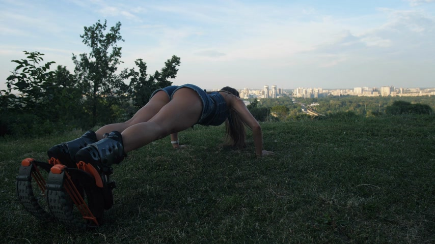 A girl on the background of the city makes squeezing on the grass in angoo jumps shoes. 4K Slow Mo Stock mozgókép