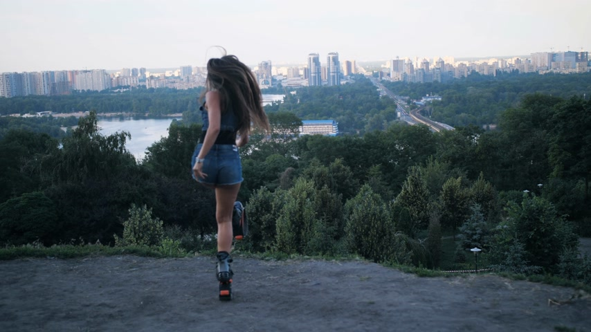 rugók : A sports girl jumping in angoo jumpsshoes and looking at the city. 4K Slow Mo Stock mozgókép