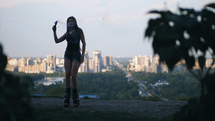 rugók : The girl dances in angoo jumps shoes in the background of the city. She has a blue smoke checker in her hands. 4K Slow Mo