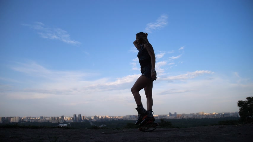 Beautiful silhouette video. Girl is dancing in angoo jumps boots against the sky. 4K Slow Mo