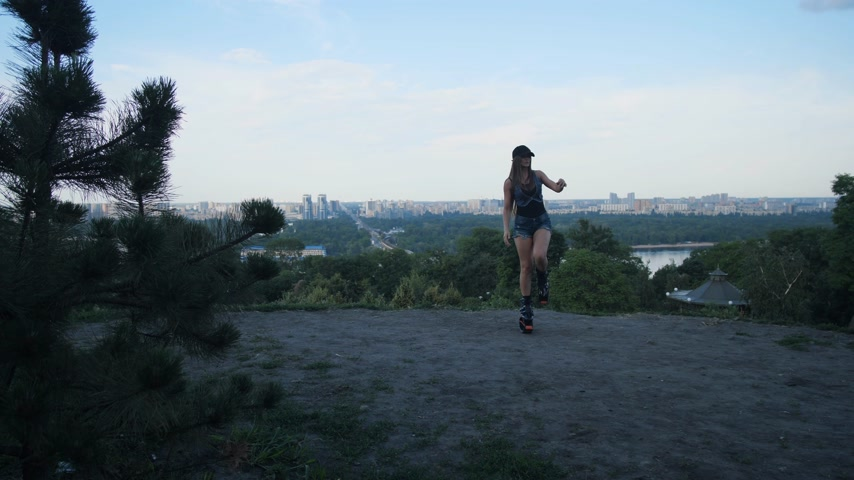 A sports girl in short shorts and angoo jumps shoes is engaged in outdoor sports. 4K Slow Mo