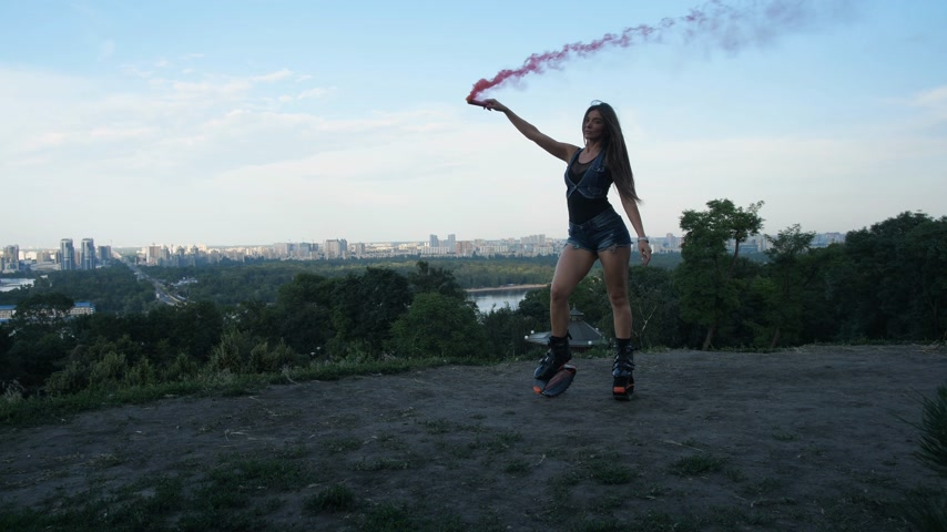 molas : Girl dancing with pink smoke in boots angoo jumps. In the park of the city. 4K Slow Mo