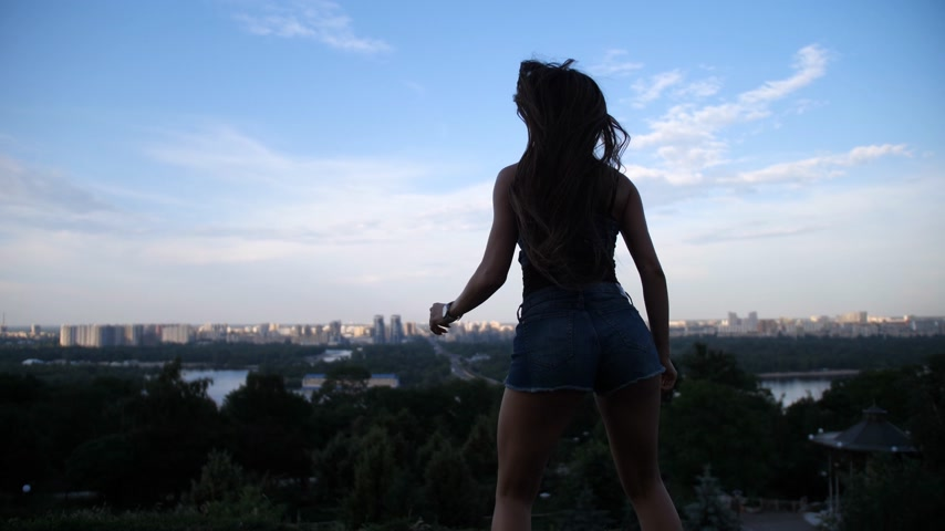 rugók : The girl jumps in the boots angoo jumps, her back to the camera in front of her overlooks the city. 4K Slow Mo Stock mozgókép
