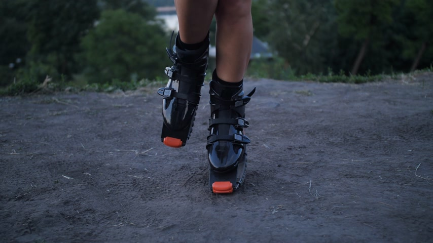 Panorama camera with shoes angoo jumps on the face of a beautiful girl who jumps in the park. 4K Slow Mo