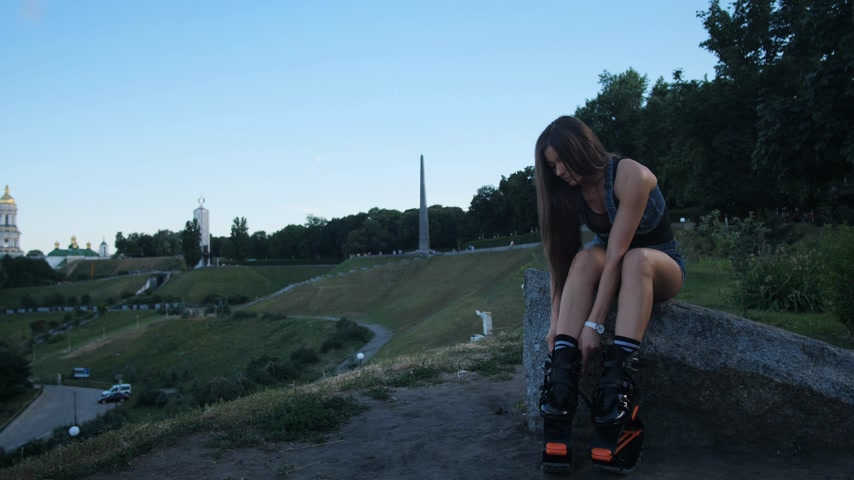 rugók : A beautiful girl dresses angoo jumps shoes. She is going to do sports in the park. 4K Slow Mo