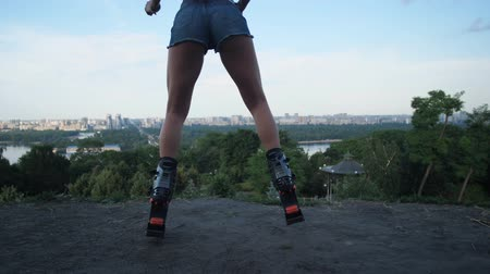 The view of the city, the movement of the camera back, in the frame appear female legs in angoo jumps boots. The girl is jumping. 4K Slow Mo