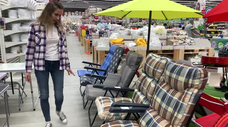 Young woman in a huge supermarket chooses a lounge chair. 4K Slow Mo Stock mozgókép